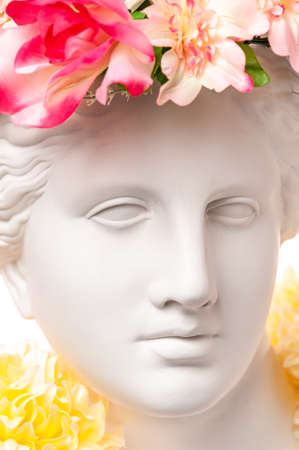 Beautiful young female face and colorful flowers. Plaster antique bust of Venus in a floral wreath. Beauty spring and summer model girl with fresh bouquet.