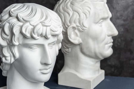 Group gypsum busts of ancient statues human heads for artists on a dark background. Plaster sculptures of antique people faces. Renaissance epoch style. Academic subject. Blank for creativity. Stock Photo