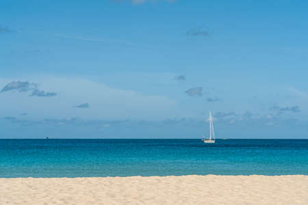 View of the white beatiful sand. Empty beach near sea on sunny day. Ocean landscape with blue sky and clouds. Yahts and fishing boat on background. Horizon. Thailand. Summer.