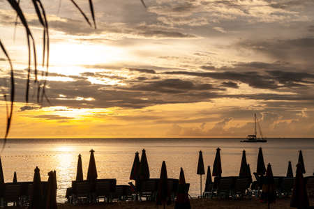 Beautiful sunset overlooking the sea and the sailing yacht that goes into the distance. Silhouettes of deckchairs against the background of the golden sky colored by sun who hidden behind the clouds. 免版税图像