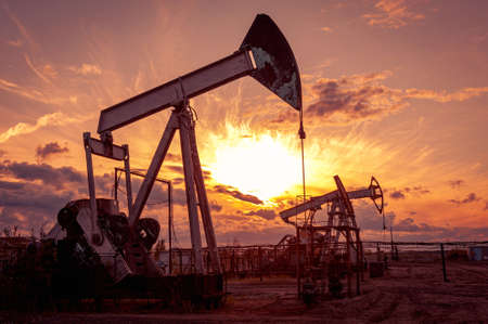 Oil pump rig. Oil and gas production. Oilfield site. Pump Jack are running. Drilling derricks for fossil fuels output and crude oil production. War on oil prices. Global coronavirus COVID 19 crisis. Banque d'images