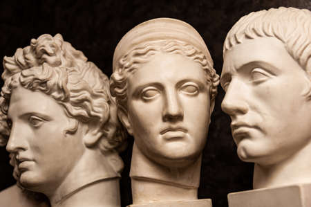 Group gypsum busts of ancient statues human heads for artists on a dark background. Plaster sculptures of antique people faces. Renaissance epoch style. Academic subject. Blank for creativity.