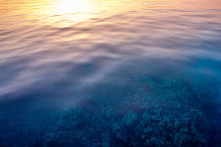 Stunning seascape on coral under clear water. Sunset with a reflection in the water taken with slow shutter. Soft Focus due to Slow Shutter. Speed Meditation. No people. Sun line. Romantic journey. Stockfoto