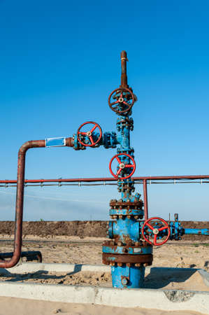 Petroleum well wellhead equipment. Hand valve with handwheel on the flow line. Oilfield site. Oil, gas industry concept. Industrial site background. Production oil. Multiple check valve gate armature. Reklamní fotografie