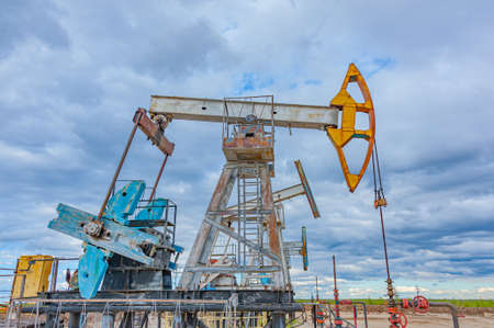Petroleum concept. Oil pump rig. Oil and gas production. Oilfield site. Pump Jack are running. Drilling derricks for fossil fuels output and crude oil production. Global crisis. War on oil prices.