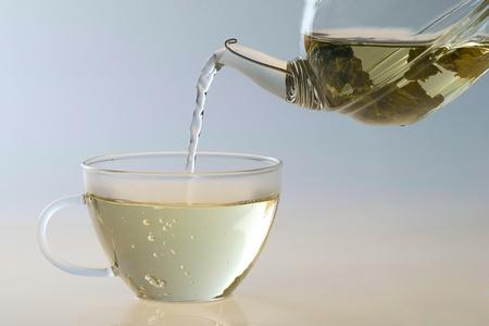 Pouring tea to a transparent teacup  photo