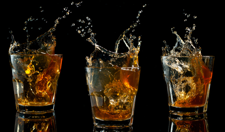 Glass of whiskey with splash, isolated on black background