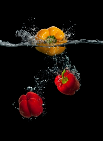 Fresh yellow and red paprika splash in water on black background photo