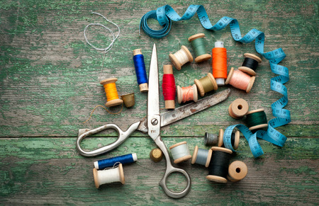 Vintage Background with sewing tools and colored tape/Sewing kit. Scissors, bobbins with thread and needles on the old wooden background Standard-Bild