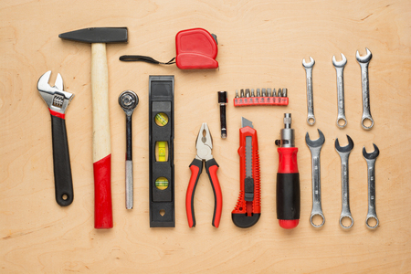 Set of hand tools on a wooden panel close up photo
