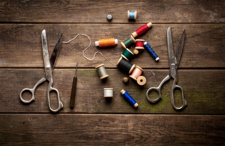 Vintage Background with sewing tools and colored tape. Sewing kit. Scissors, bobbins with thread and needles on the old table.