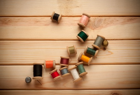 sewing kit: Sewing kit. Scissors, bobbins with thread and needles on the old background