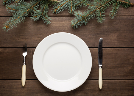Vintage or rustic christmas table setting from above. Elegant empty white plate. photo
