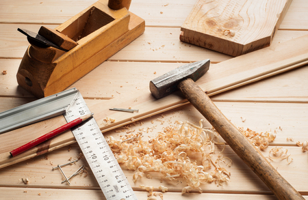 carpenter items: carpenter tools,hammer,meter, nails,shavings, and chisel over wood table
