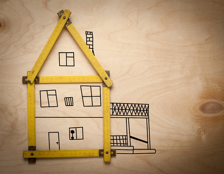 A house concept with yellow meter on wooden background photo