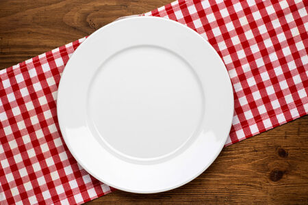 Empty plate on wooden tabletop with tablecloth close up Zdjęcie Seryjne