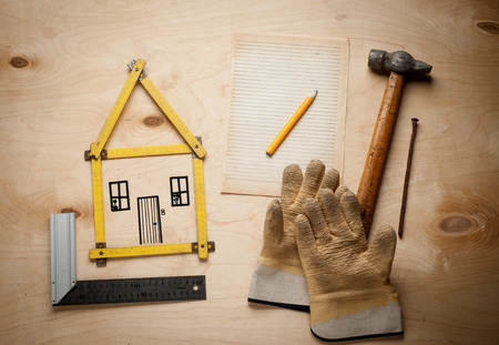 House concept with yellow meter and working gloves on wooden background