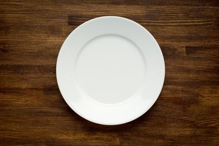 plato de comida: Placa blanca vac�a en la mesa de madera de cerca Foto de archivo