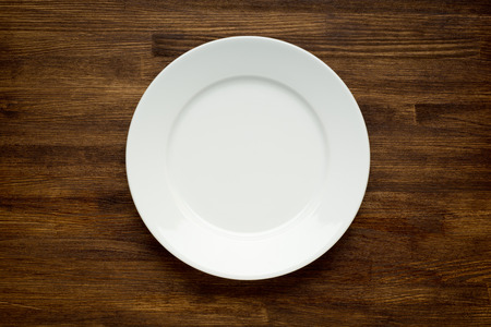 Empty white plate on wooden table close up