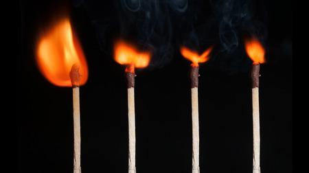 unlit: A lit matchstick close to an unlit matchstick