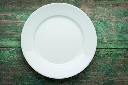 grunge flatware: Empty white plate on wooden table close up