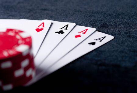 jeu de carte: quatre as élevés sur la table noire avec des frites sur fond noir Banque d'images