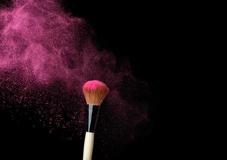 powderbrush on black background with blue powder splash  close up