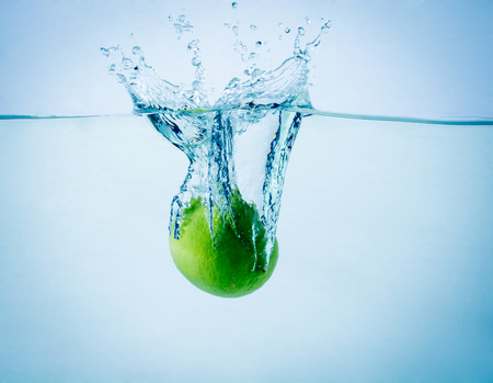 action shot: High speed freeze action shot of a lime splashing into water