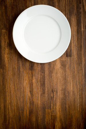 grunge cutlery: Empty white plate on wooden table close up