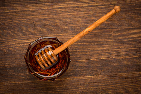 Fresh natural honey in a jar with honey spoon on a wooden rustic vintage table