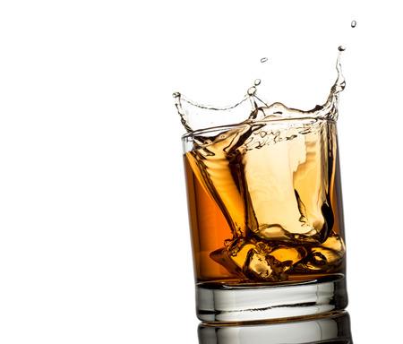 osolated: splash of whiskey with ice osolated on white