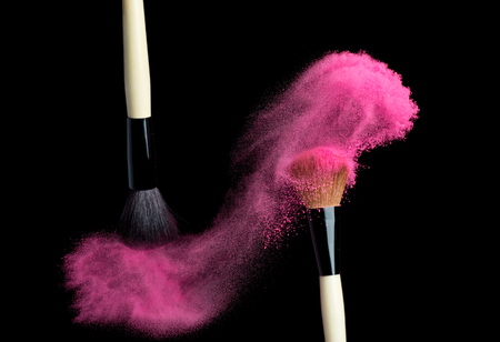 Make up brush with pink   powder splash isolated on black 写真素材