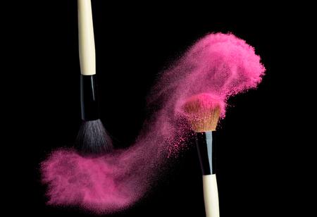 brush: Make up brush with pink   powder splash isolated on black Stock Photo