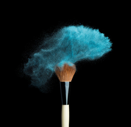 Isolated make-up powder with brush on black background Stock Photo
