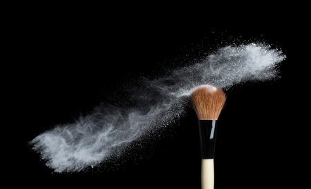 Make up brush with white powder splash isolated on white