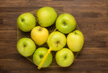 heap of apples in the net bag from the store on wooden background photo