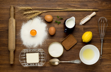 složení: Pečení dort ve venkovské kuchyni - těsto recept složek (vejce, mouka, mléko, máslo, cukr) na vinobraní dřevěný stůl shora. Layout pozadí s volným prostor pro text. Reklamní fotografie