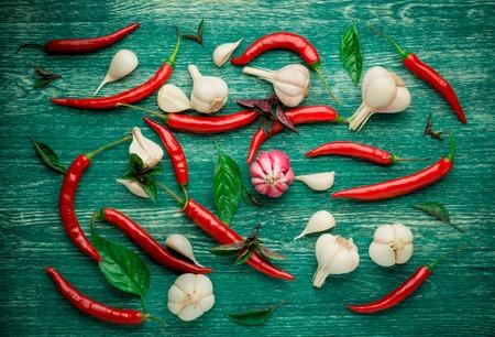 comida italiana: Pimientos de chile rojo, ajo y albahaca sobre un fondo de madera. Foto de archivo
