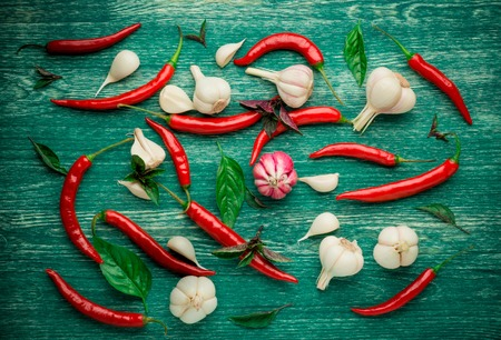 chili: Red chili peppers, garlic and basil over a wooden background. Stock Photo