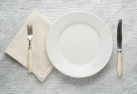 cubiertos de plata: cuchillo de la placa y el tenedor sobre la mesa de madera.