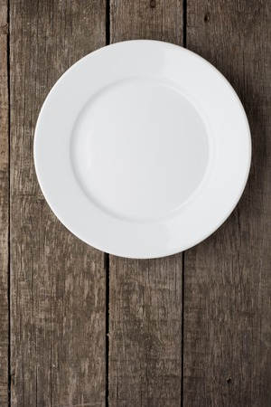 Empty plate on old wooden background. Top view.
