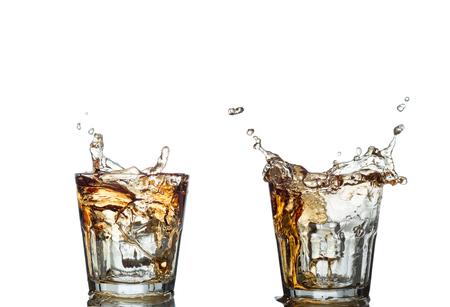 bebidas alcohÓlicas: splash of whiskey with ice osolated on white. Foto de archivo