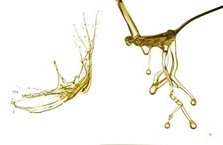 oil splash: Pouring oil splash on spoon. Isolated on white background. Stock Photo