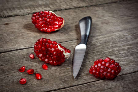 pomegranate: Fresh pomegranate with knife on rustic wooden background .
