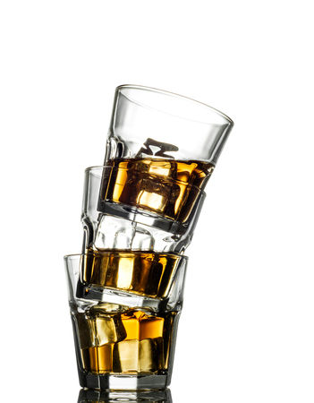 whiskey on the rocks: Three glasses of whiskey on the rocks, one on top of the other.