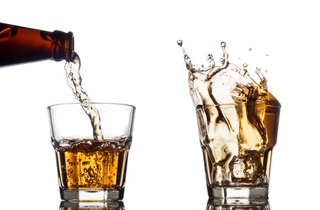 Pouring whiskey in a clear glass, on white background.