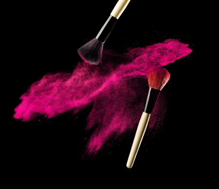 woman close up: Make-up brush with pink powder explosion on black background.