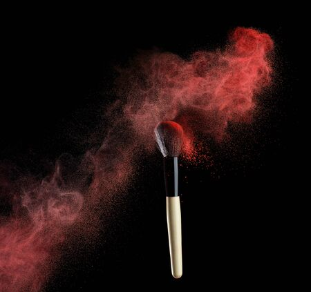 skintone: makeup brush with red powder isolated on white.