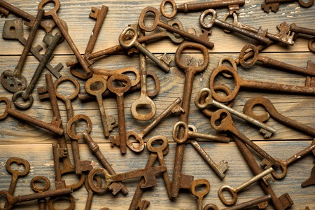 tresspass: Many old keys on a well used old wooden desk. Stock Photo