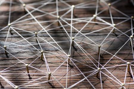 entities: Linking entities. Network, networking, social media, internet communication abstract. A small network connected to a larger network. Web of gold wires on rustic wood. Stock Photo